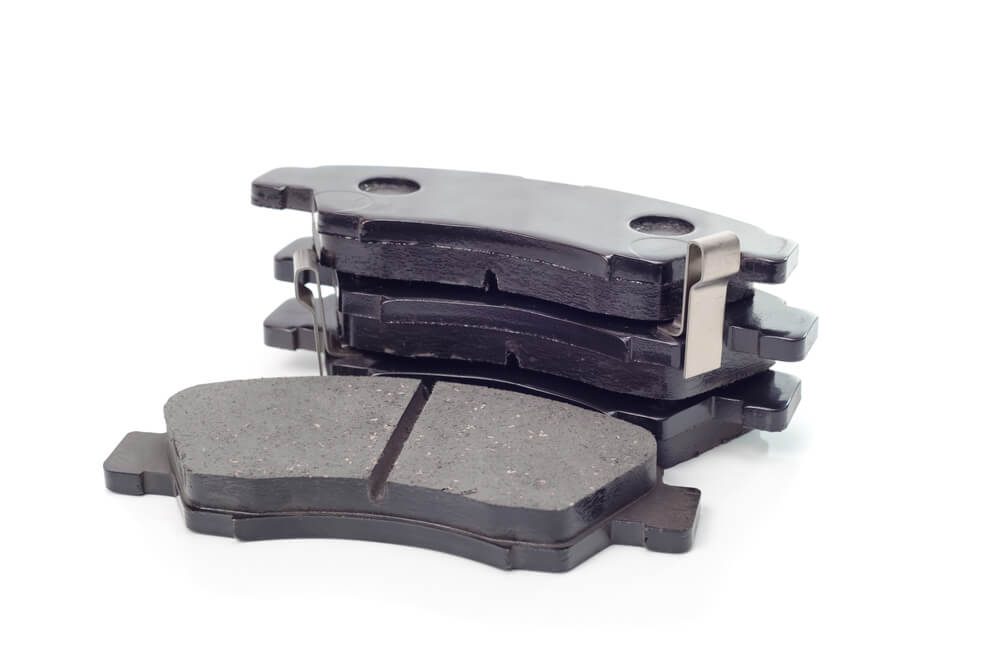 automotive brake pads. Isolated on white background - why your SUV squeaks