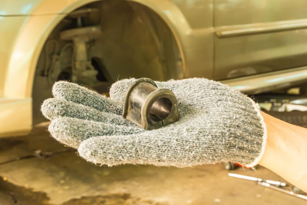 Hand with Car suspension stabilizer bush