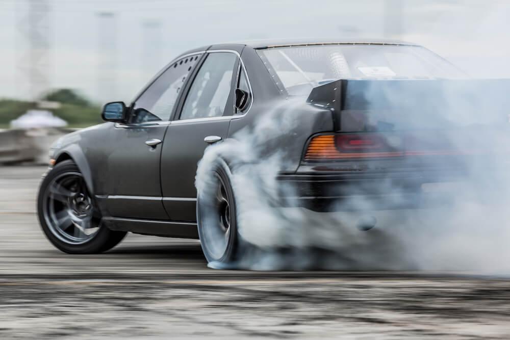 Car drifting, sports car wheel drifting and smoking on track.