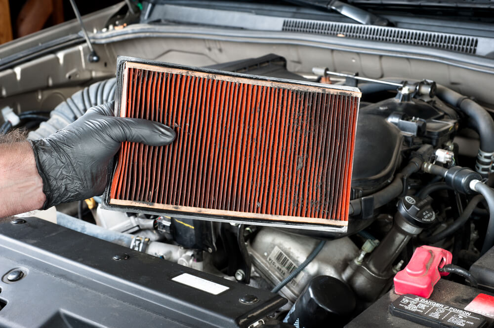 a mechanic holding a dirty air filter - luxury cars bad mileage