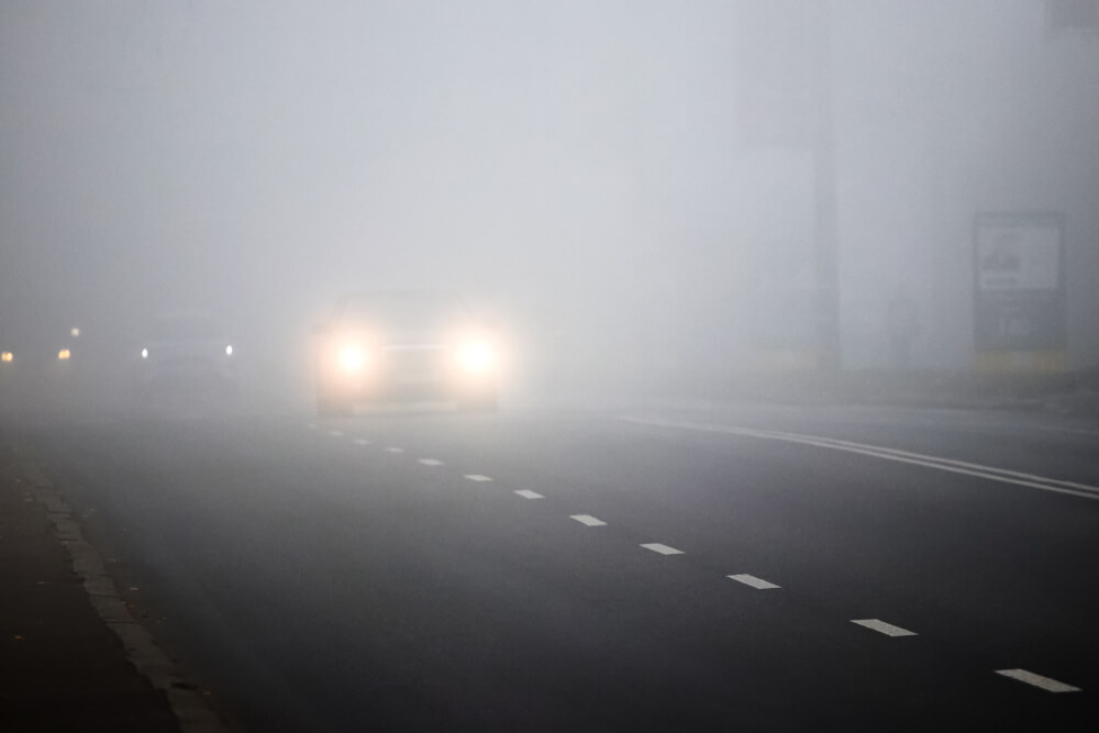 Motion of cars with headlights on during heavy fog