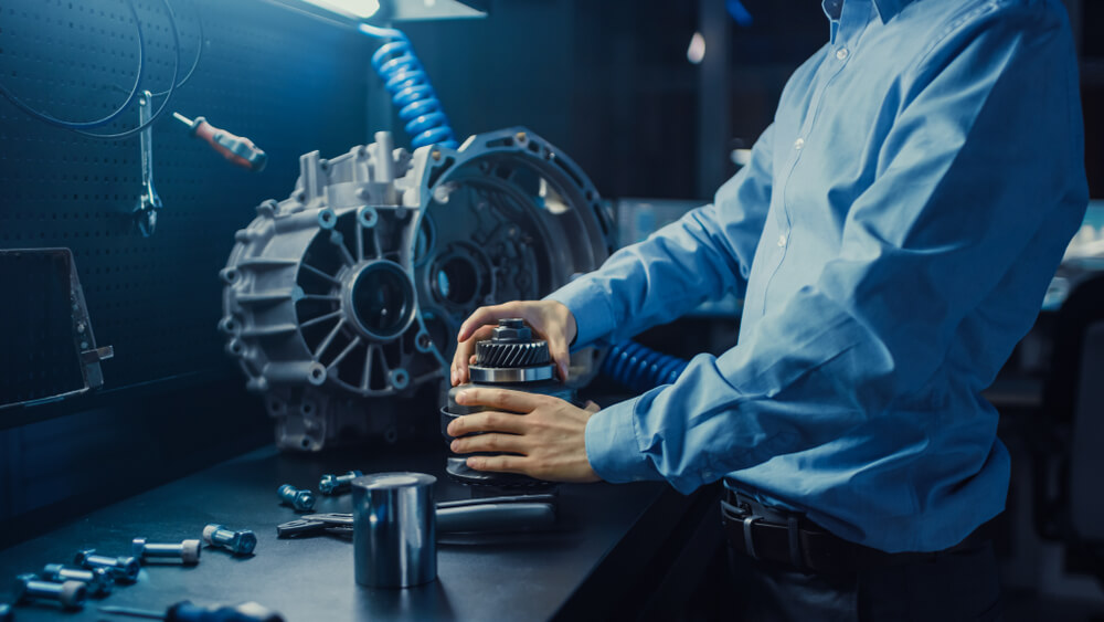 mechanic holding a gear at a service center. - luxury cars bad mileage