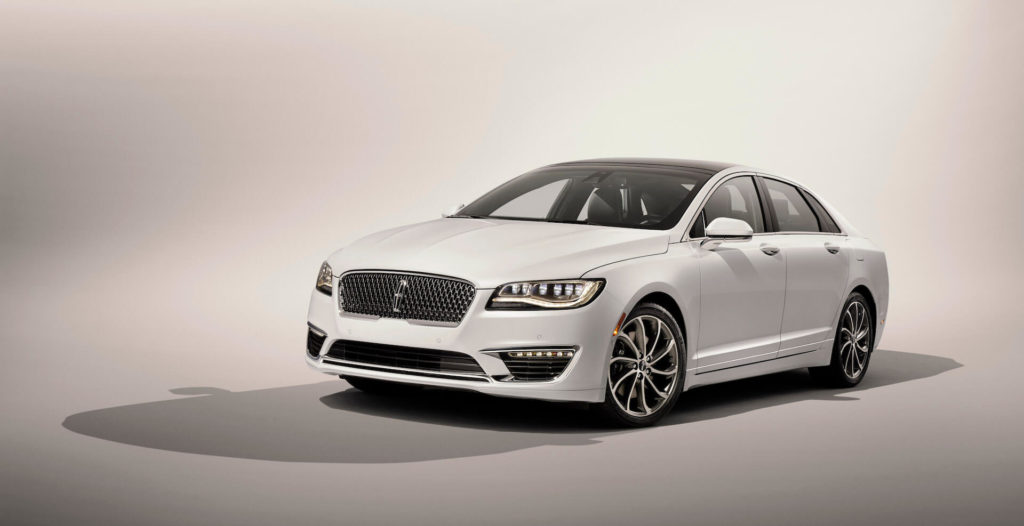 front side view of a white 2020 Lincoln MKZ Hybrid, isolated, grey background.