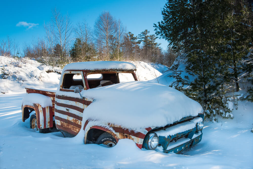 Old pickup truck painted red white and blue sitting in the forest abandoned and covered in fresh snow - pickup trucks rust