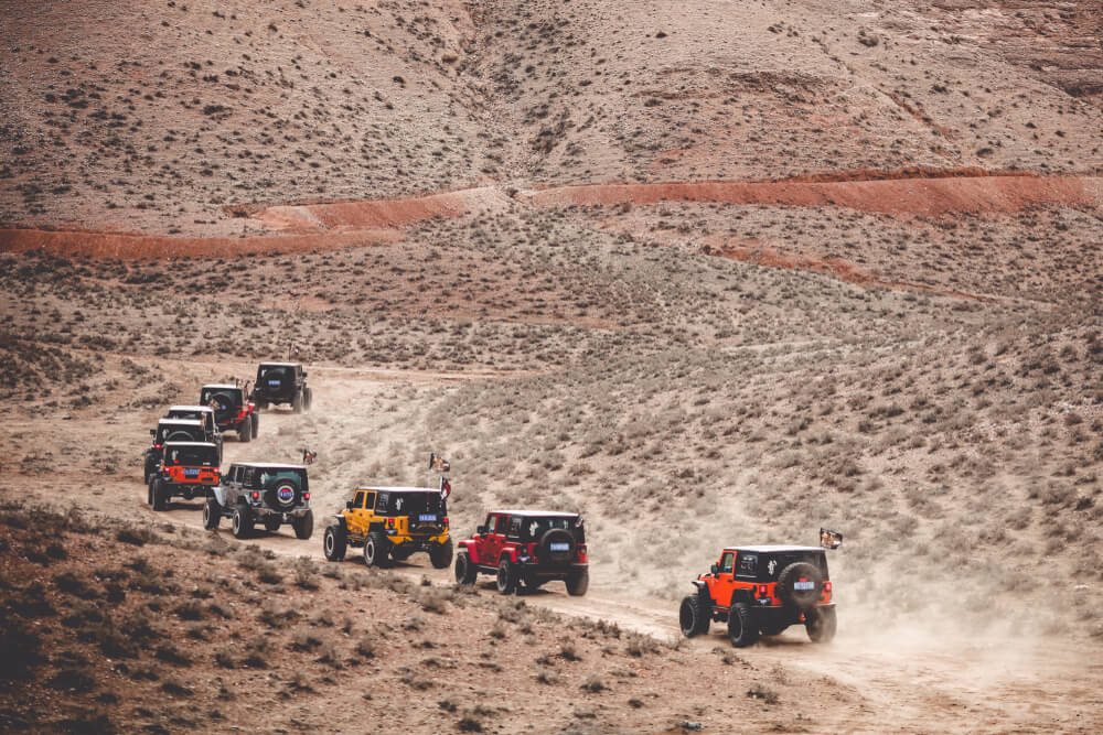 a line of red, orange, and yellow jeeps in a deserted mountainous area. - trucks and jeeps