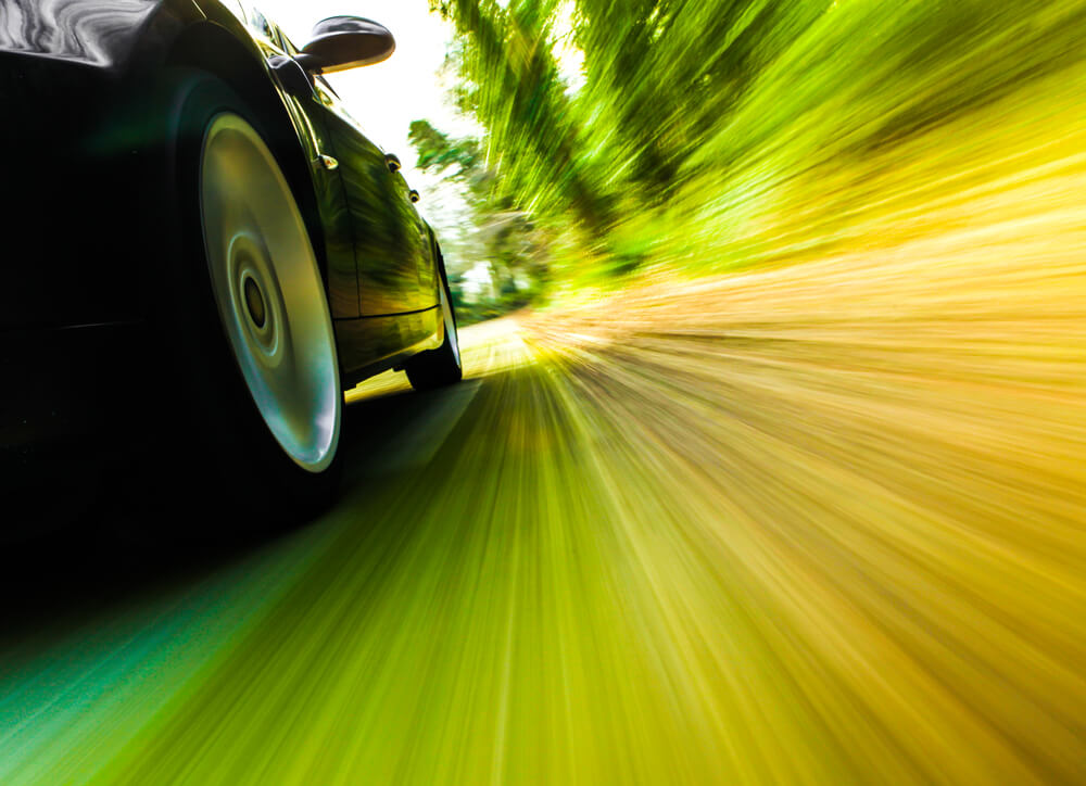 side view of wheels of a car going too fast, motion blur. - luxury cars bad mileage