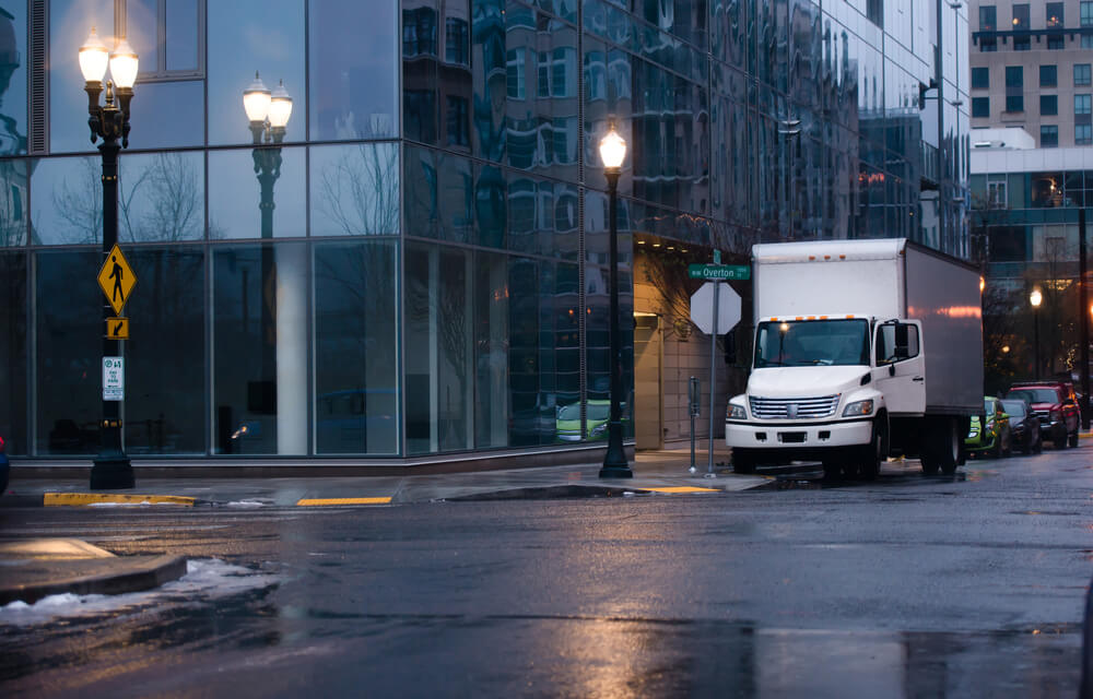 white box truck in a wet city street.