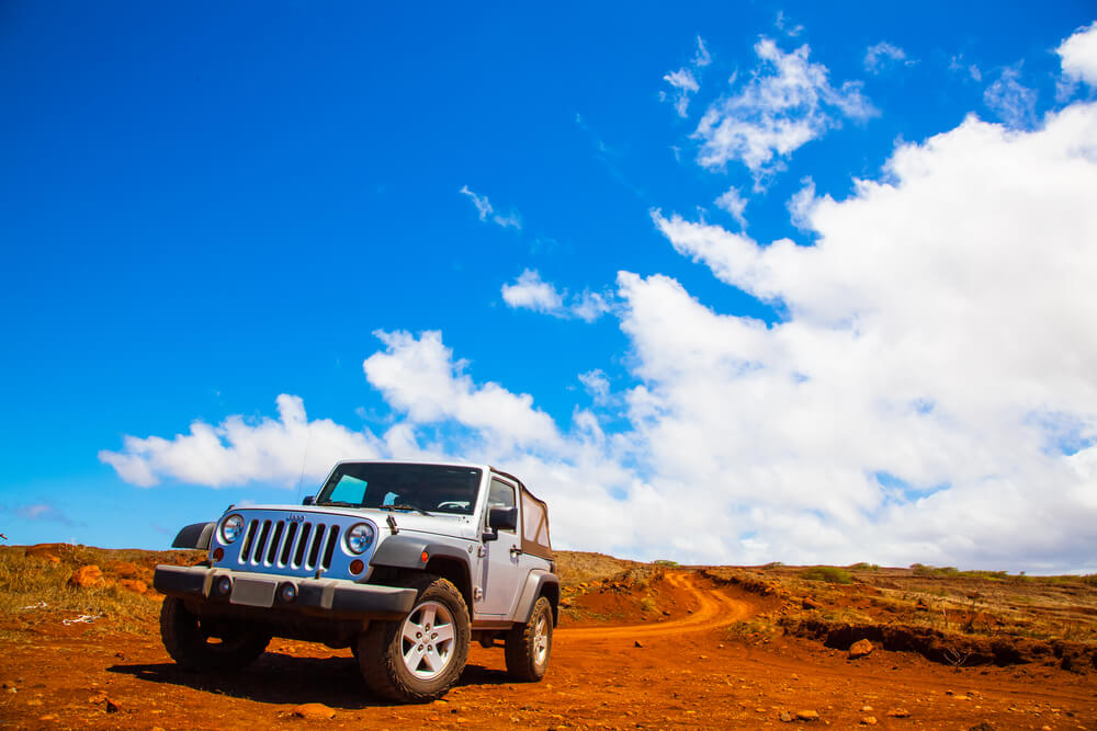 a white Jeep Wrangler in a deserted area. - trucks and jeeps