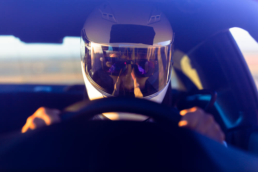 professional racer wearing a helmet behind the wheel, inside a racecar